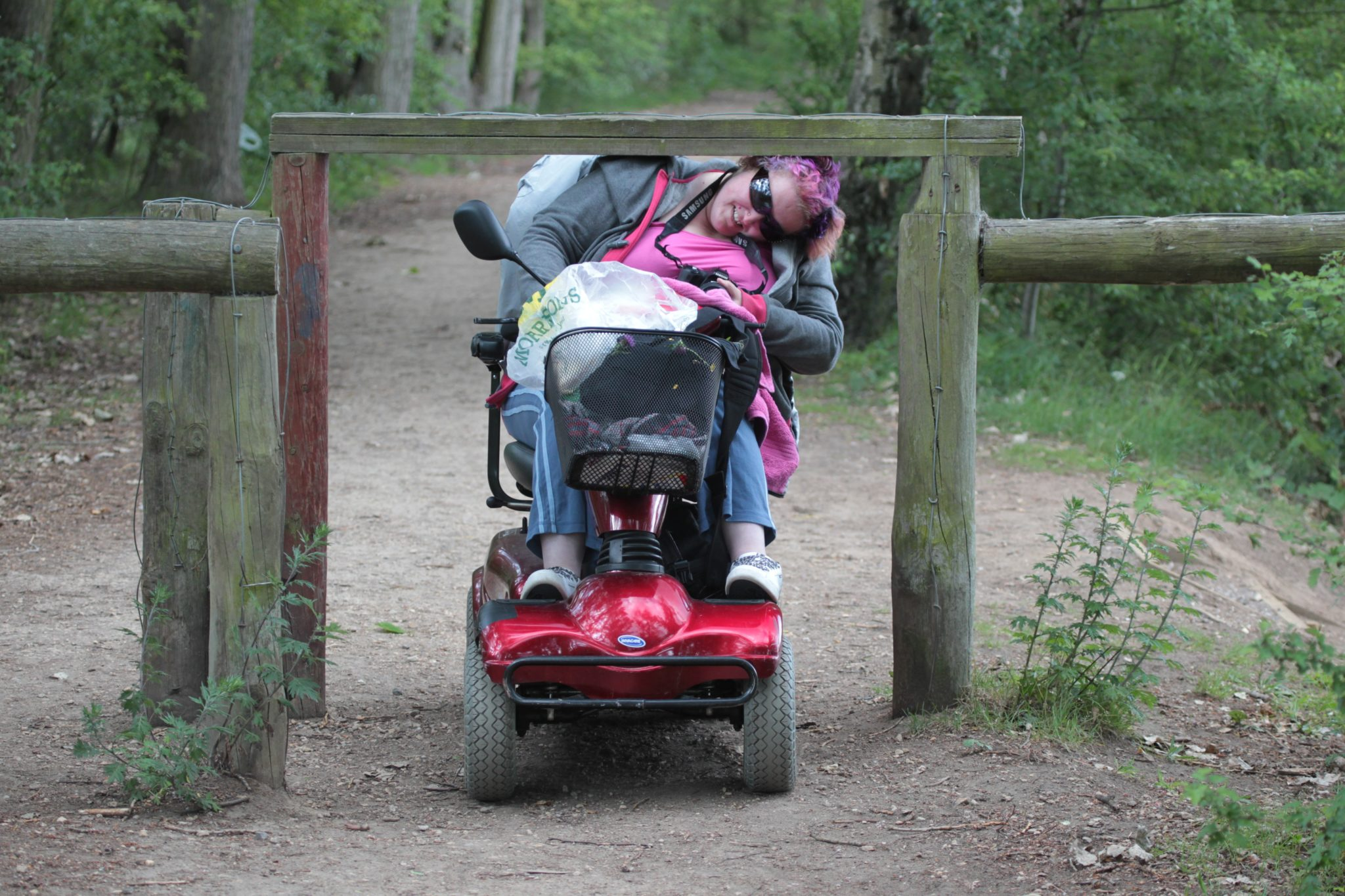 Woman on vehicle ducking underneath a fence